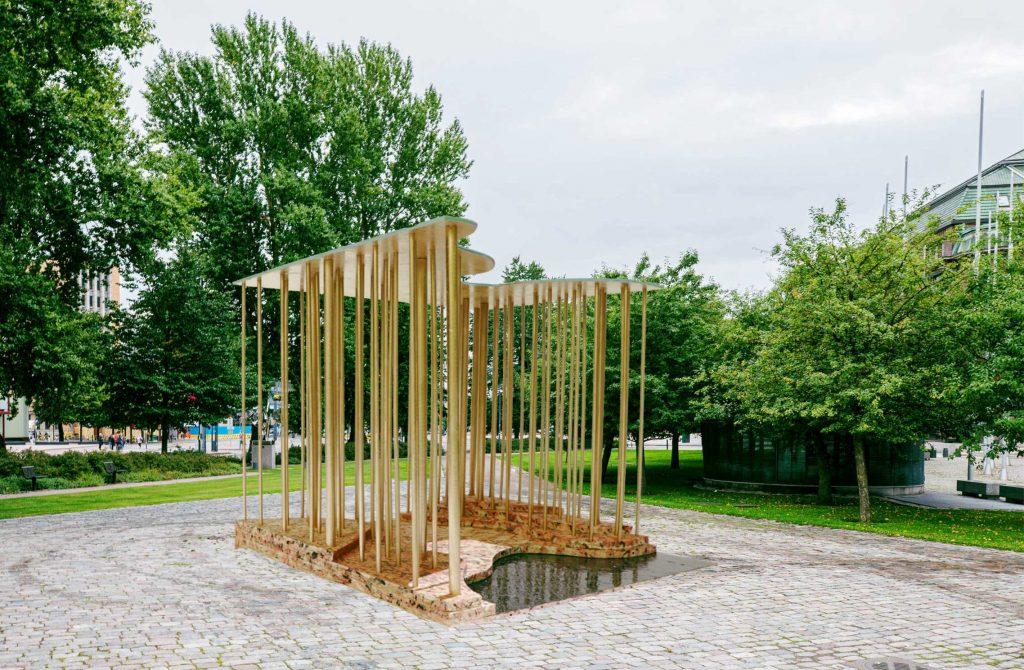 Skogen som utgörs av de gyllene pelarna är som den finska demokratin, som bärs upp av många stammar, även tunna, som tillsammans bildar en stark gemensam struktur för att bära monumentets tunna gyllene tak.